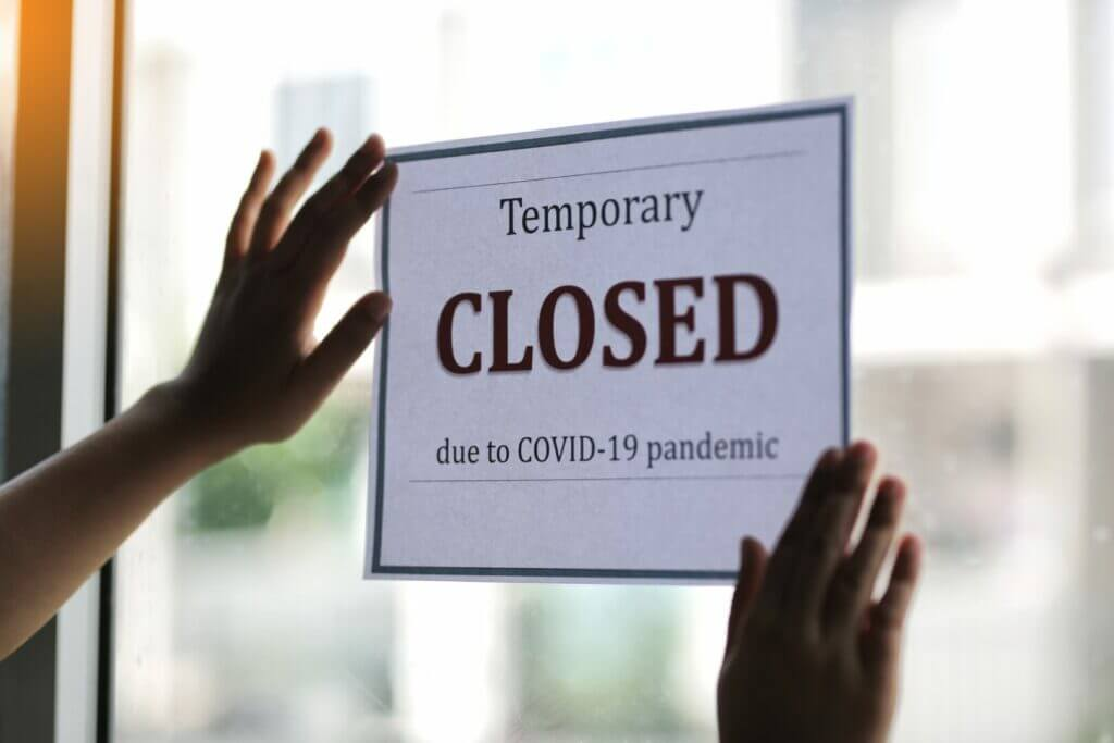 """A woman taping a side onto her window that says """"temporary closed due to COVID-19 pandemic"""""""