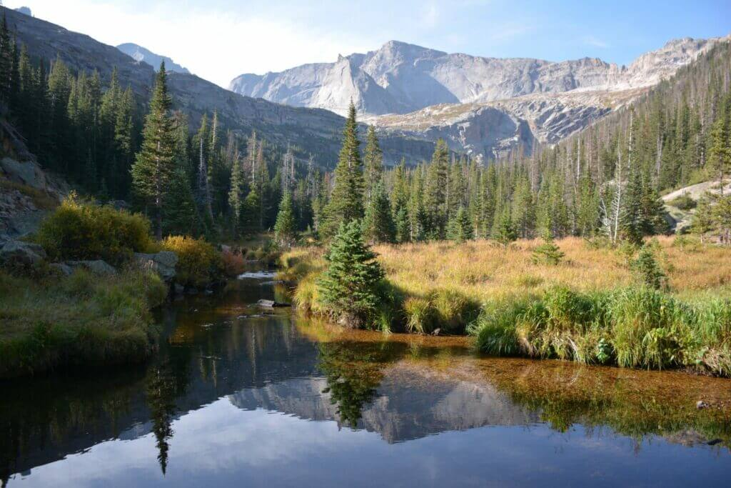 A still lake with trees and mountains in the background. You have to make a national park reservation to get into Rocky Mountain National Park
