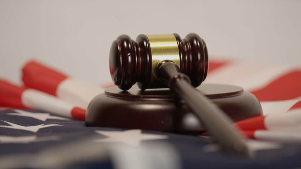 Gavel laying on a USA flag. The lawsuits with Camping World might leave you with good sam regrets