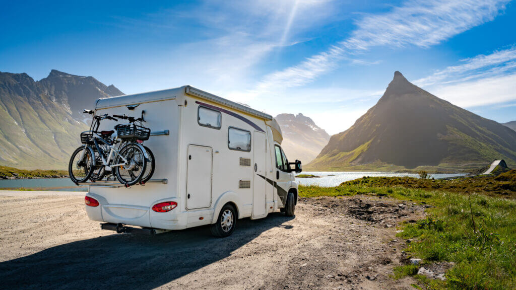 An RV is dispersed camping along a lake and some gorgeous mountains.