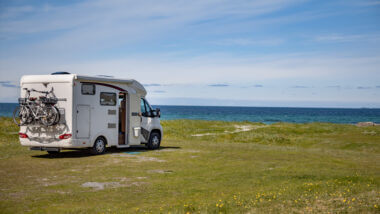 An RV is parked in an empty field for dispersed camping along the ocean coast.