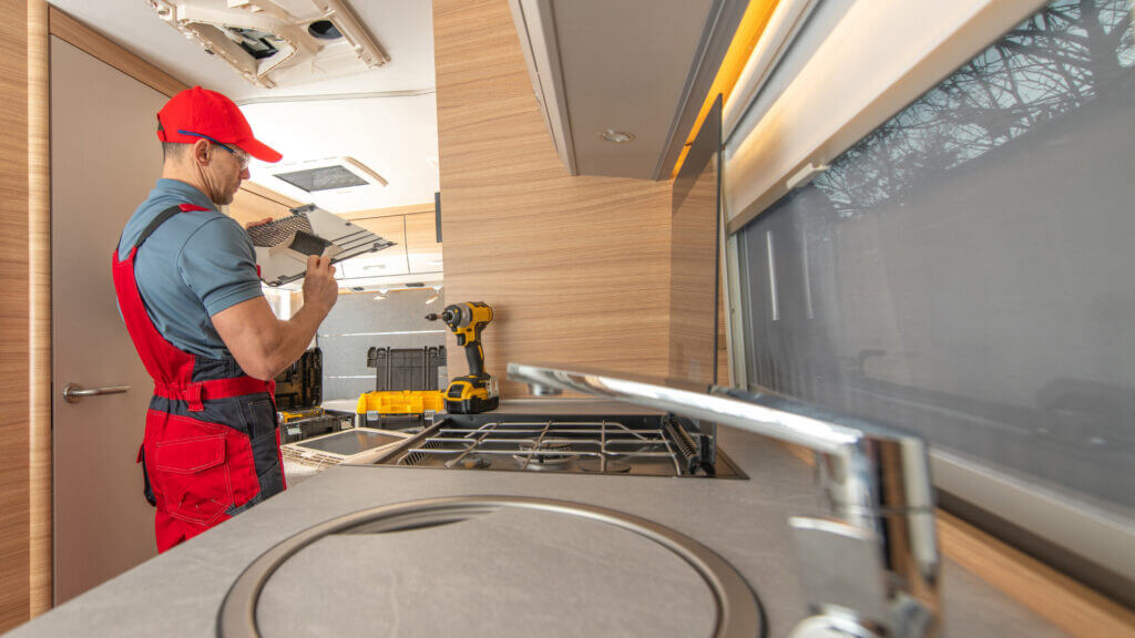 Unexpected repairs can be a very expensive RV ownership cost. A man fixes something in the ceiling and inspects the parts.