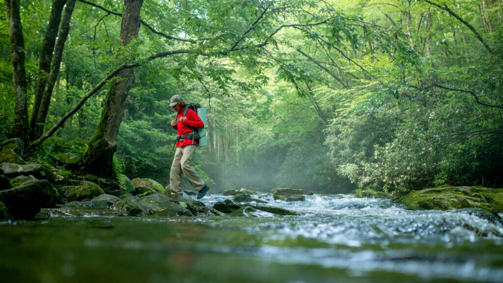 A very green river setting in the Smoky mountains and a man crosses the river with a large camping backpack on.