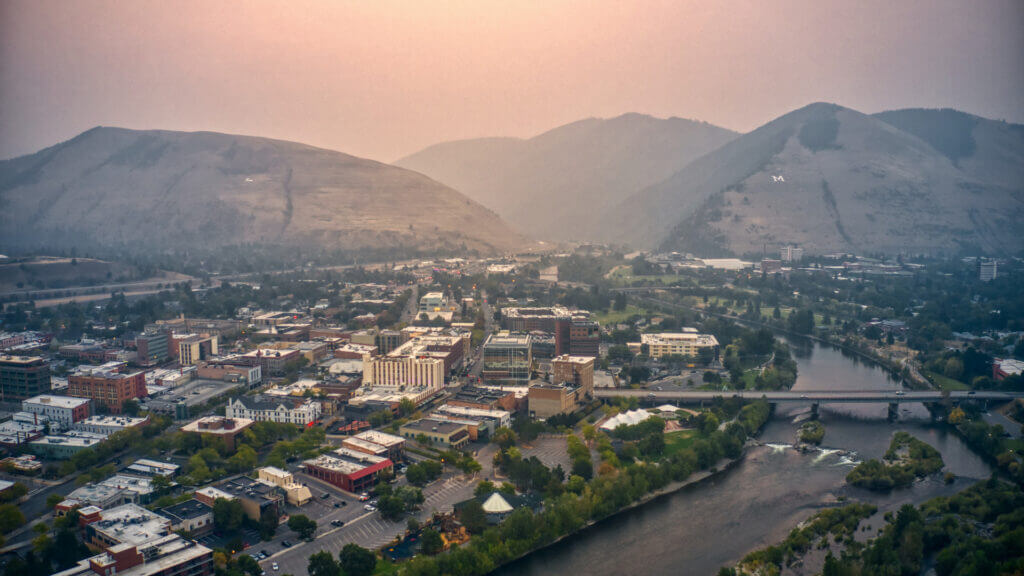 Missoula, Montana is a gorgeous city in Big Sky country with large hills and a river running through it.