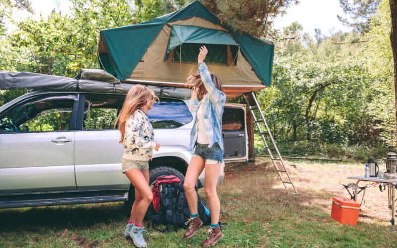 Two girls dance at the campsite because their camping playlist rocks!