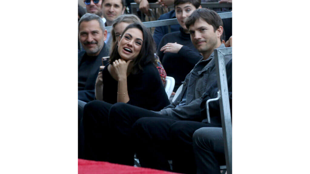 Mila Kunis and Ashton Kutcher smile while sitting in a crowd at a Hollywood Walk of Fame event. They enjoy the RV life to escape the fame sometimes.
