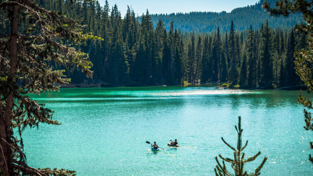 Two kayakers venture out along a turquoise glacier lake just outside of Bend, OR.