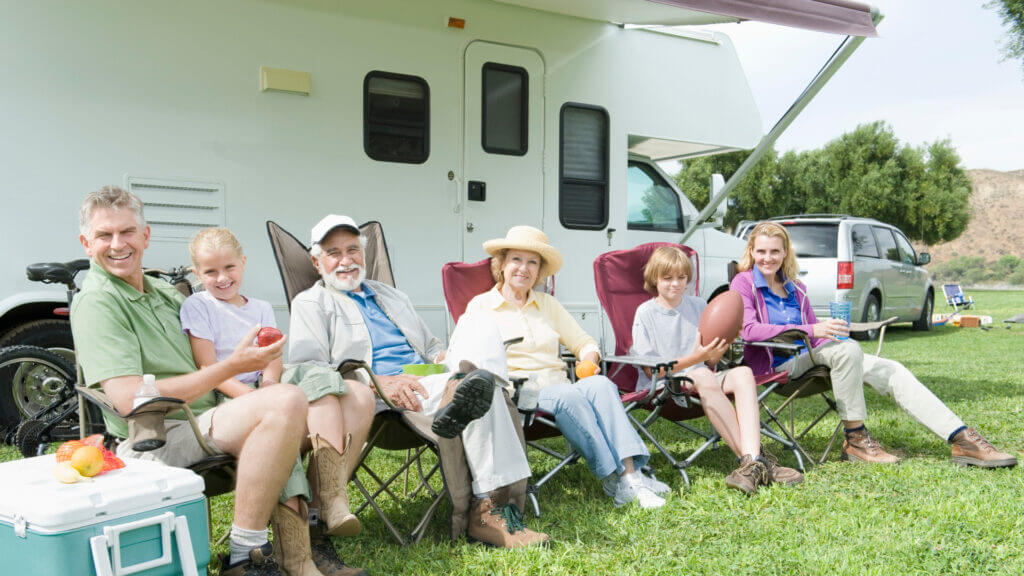 An FMCA is targeted towards an older RVer demographic. A family of RVers sit alongside their motorhome in camping chairs.