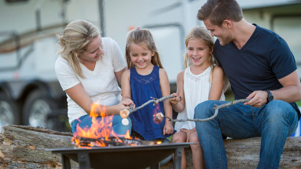 A family roasts marshmallows around a campfire pit outside of their fifth wheel rv.