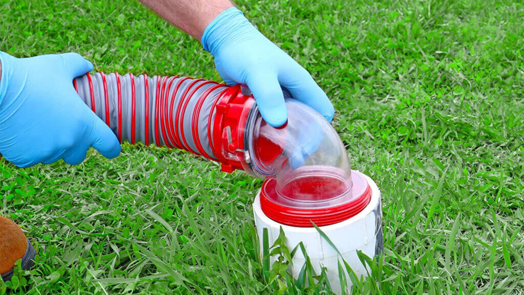 A man with blue gloves uses a viper sewer hose kit to dump his RV's waste tanks.