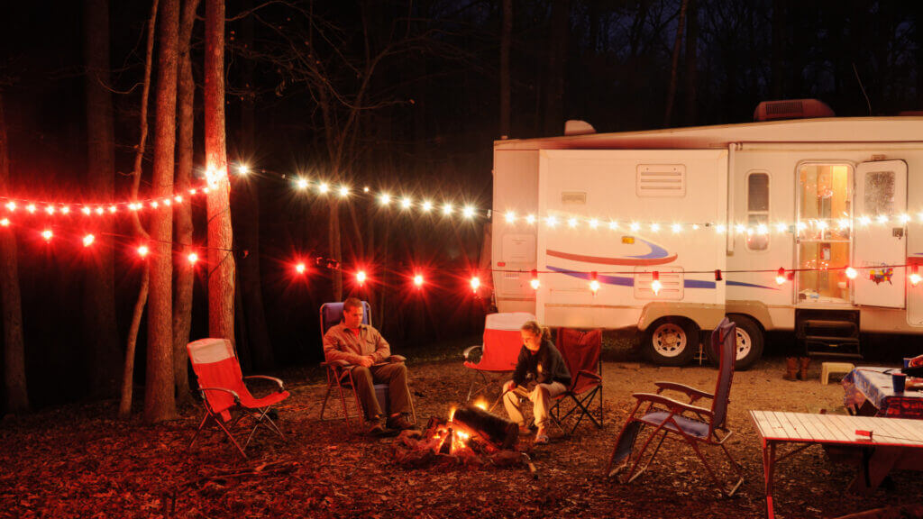 A couple enjoy a fire pit under some lights in the campground with the RV lit up behind them. All of those electronics are protected with a Surge Guard 50 amp surge protector.