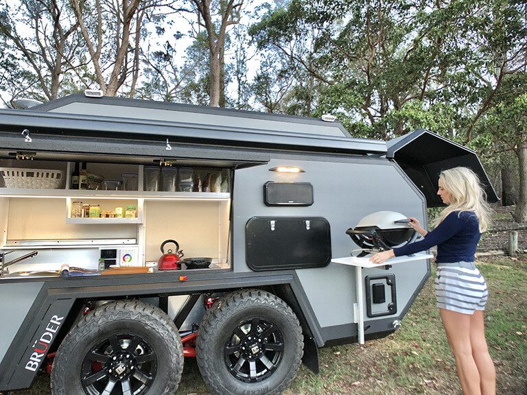 Woman cooking outside of her off-road trailer
