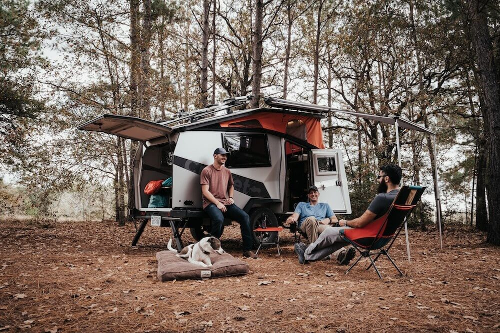 Three men and a dog sitting outside in the woods with their off-road trailer in the background
