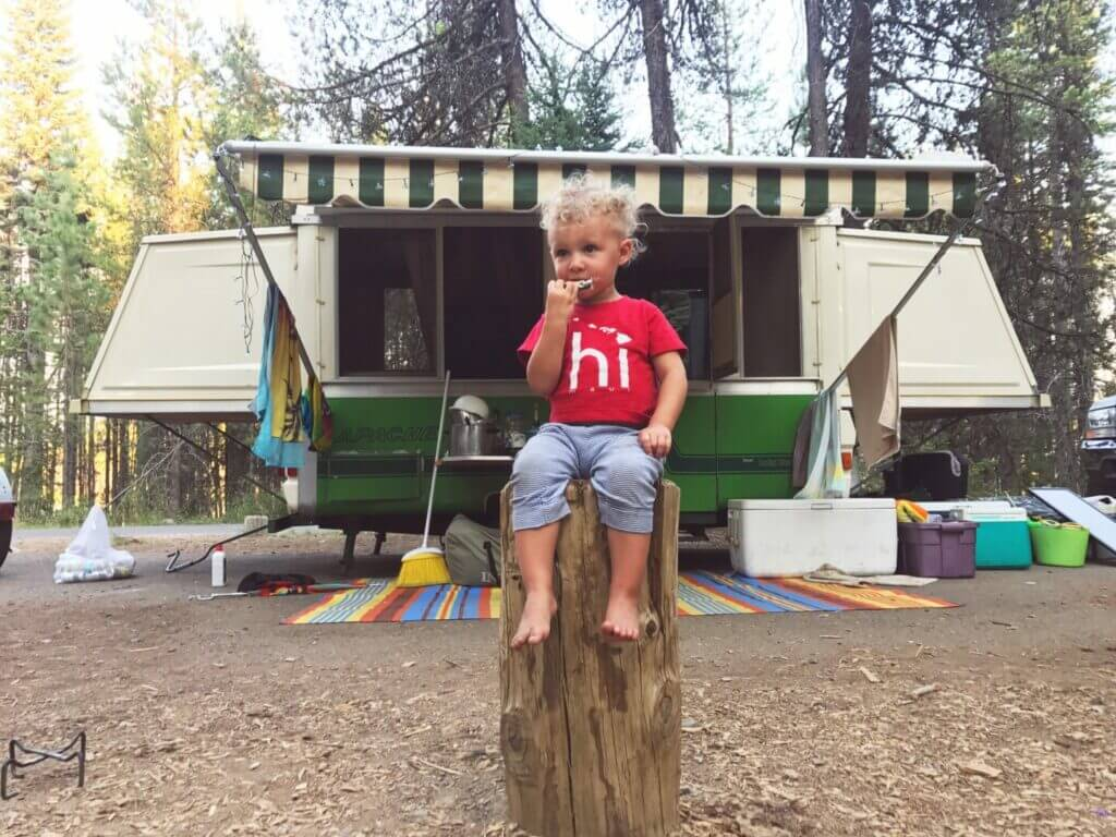 toddler sitting on a stump playing with a toy camper and a real a pop up camper behind him.