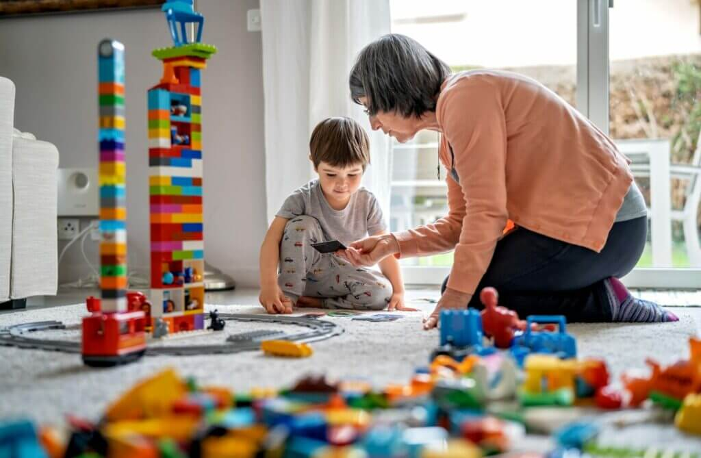 Little toddler boy playing with grandmother with Lego bricks, a toy camper lego set would be perfect for him