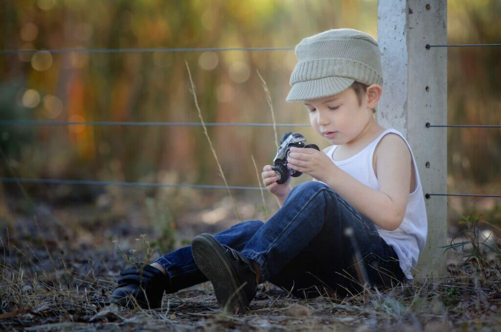 a little boy sitting by a fence playing with a toy truck. The perfect addition would be a toy camper for that toy truck.