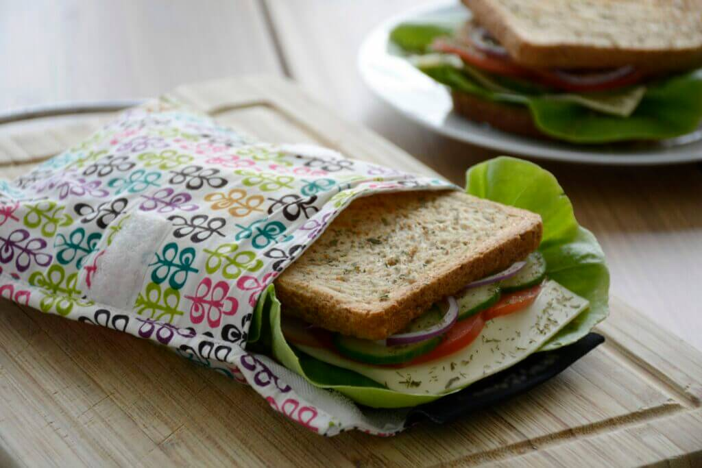 A sandwich ready to pack inside a reusable bag sitting on a cutting board. You'll want to pack food when planning your RV Trip To Disneyland.