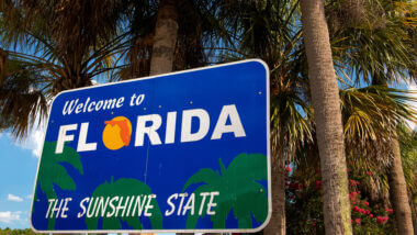 Florida sign for the sunshine state set against some palm trees. Where are the best free camping spots in Florida?