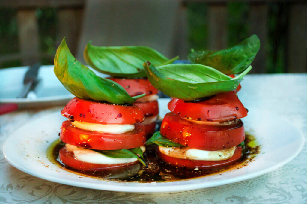 Tomato, mozzarella cheese, and basil stacked on a white plate. This is one of our favorite no cook camping recipes.