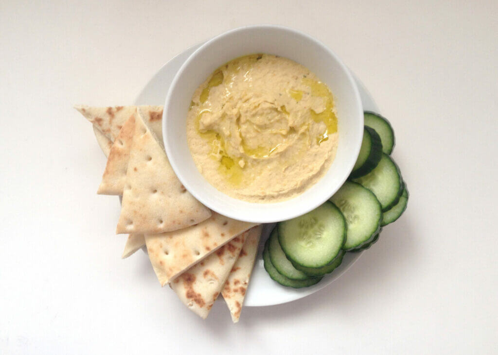 Pita slices and hummus with cucumbers on a plate. This is one of the easiest no cook camping recipes.