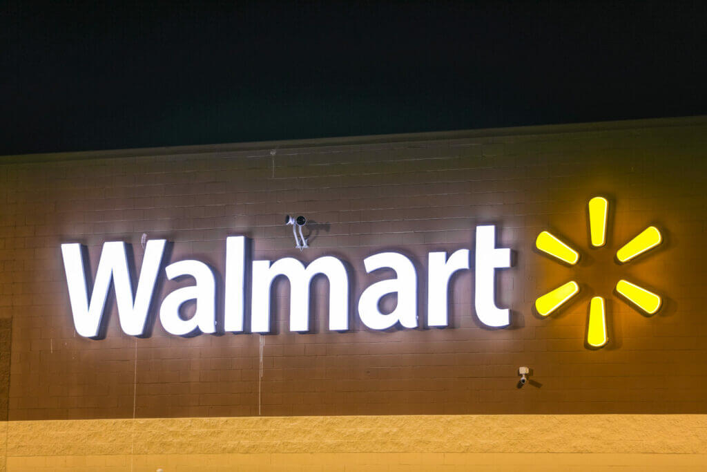 Lit up Walmart sign outside of a store. You can go in person to get your Walmart fishing license
