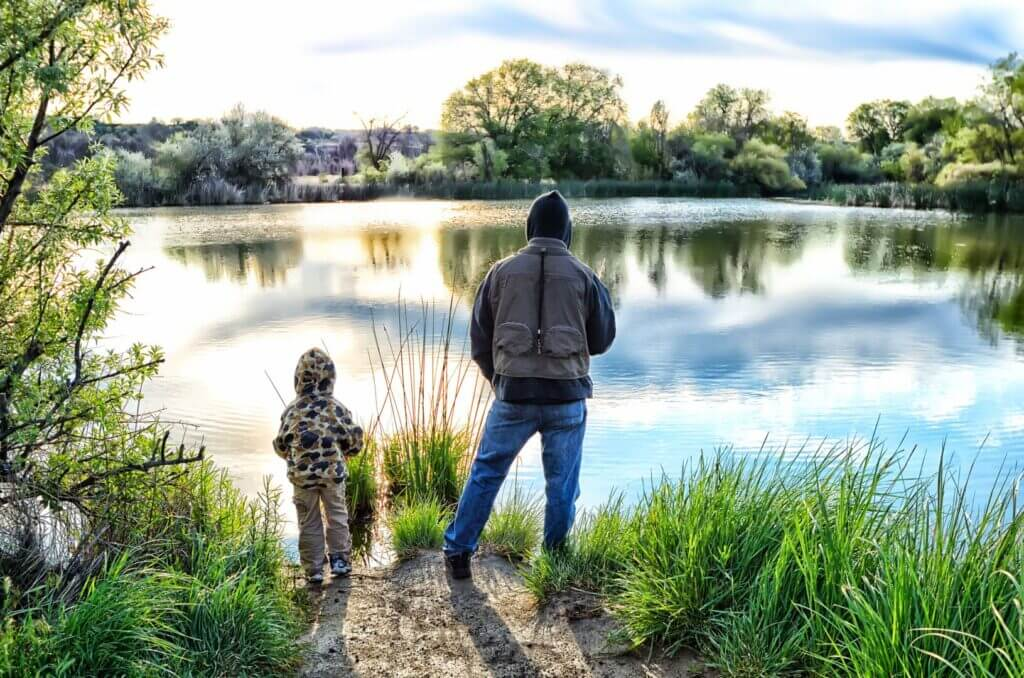 A dad and his son fishing in a calm lake. He got his Walmart fishing license before coming here.