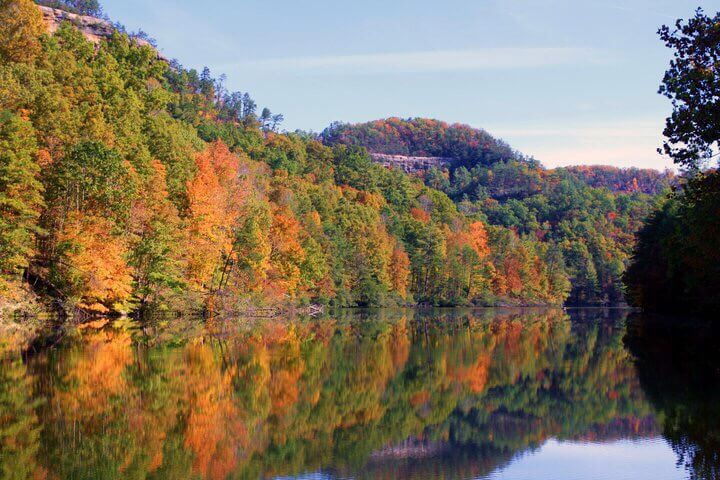 A lake with fall colored trees near red river gorge camping