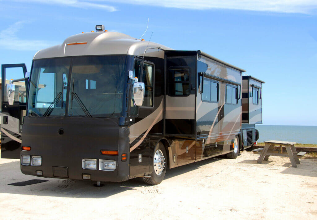 Exterior shot of RV with slides out parked at the beach