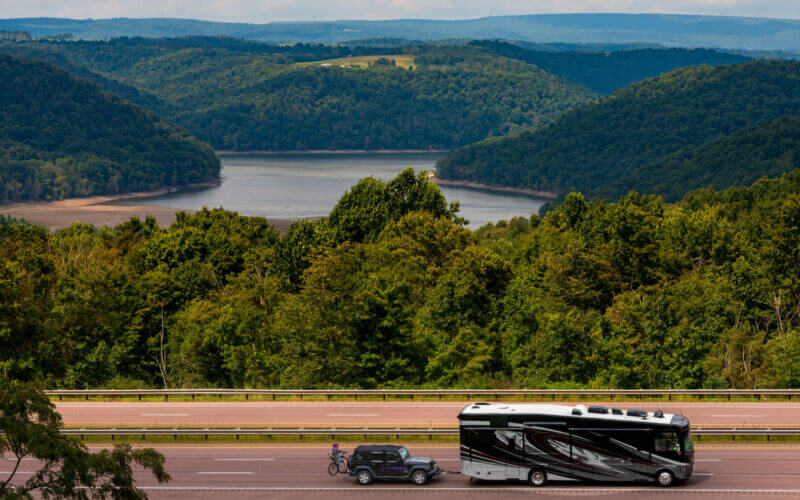 rv with slides in driving down the highway with a beautiful lake view behind it