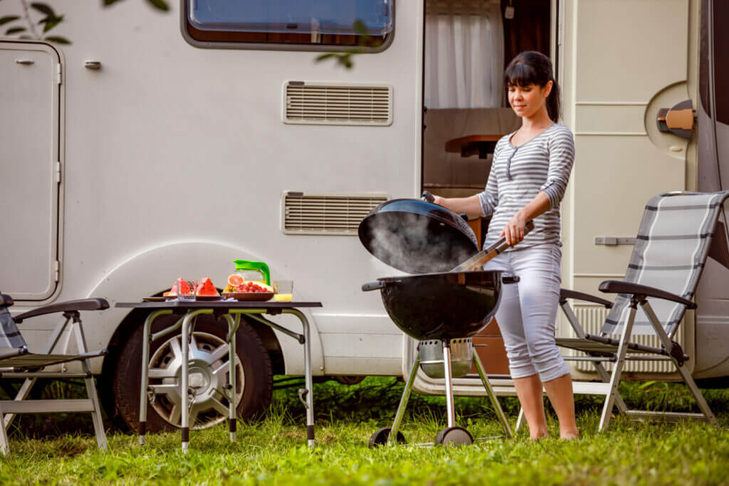 Woman grilling her barbecue outside of the RV listening to her RV stereo
