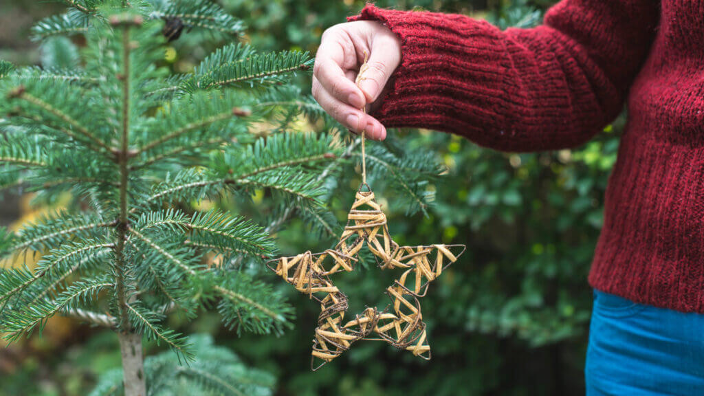 A woman holds a handmade ornament in front of pine tree.