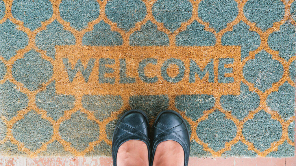 A woman stands on a welcome mat that could be made better for your traveling friend by getting a personalized camping one.