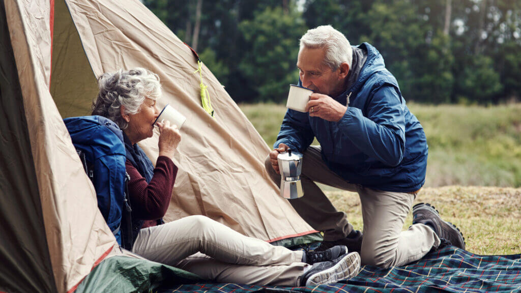 An older couple sip on coffee outside of their tent with personalized mugs.