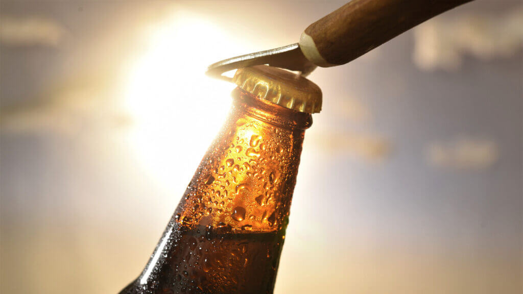 A bottle is being opened against the sun and a bottle opener is the perfect gift for the camper in your life.