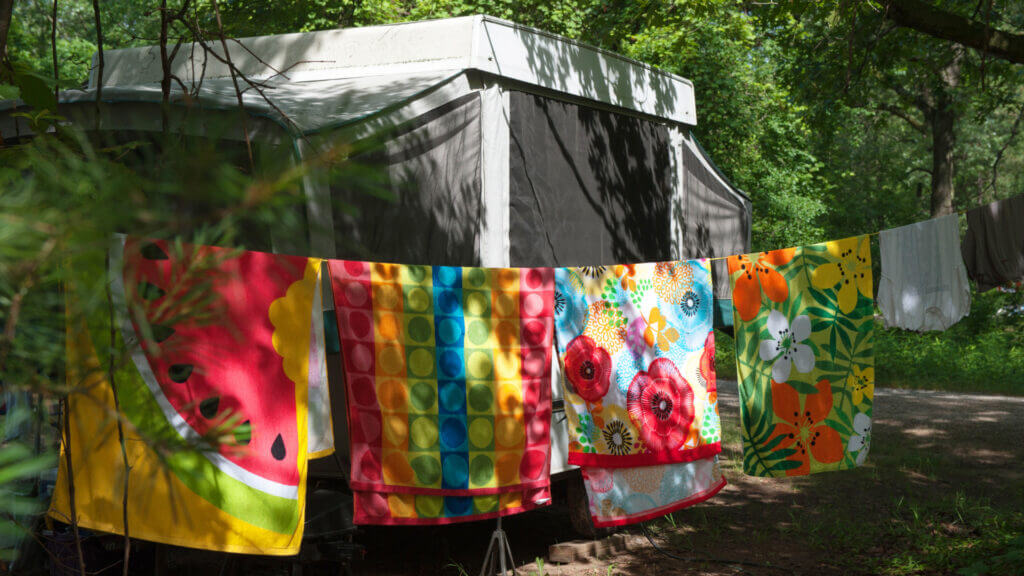 A line of beach towels hangs in front of the camper but you'll never lose them if they're personalized!