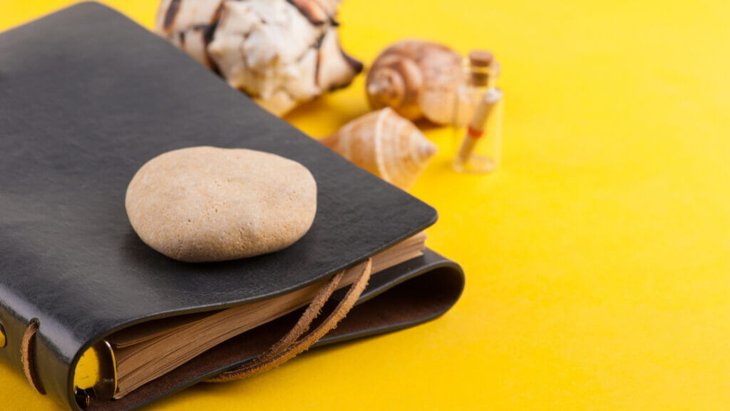 A leather bound notebook with shells and a rock is a great gift for the traveler friend who can write down all of their adventures.