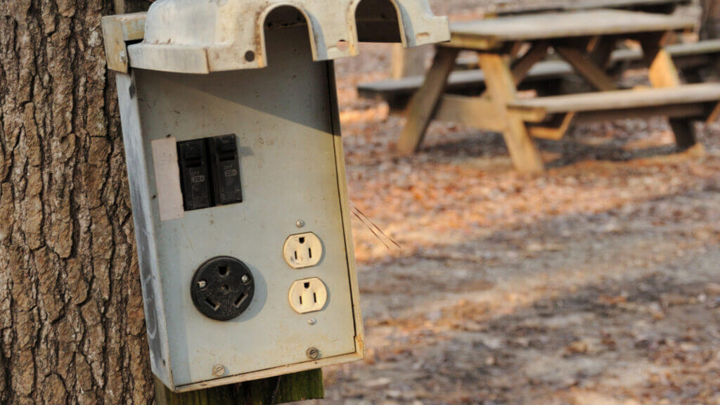 A campsite has the RV electrical hookup against a tree. Protect your RV electronics with a Camco Power Defender 50 amp surge protector.