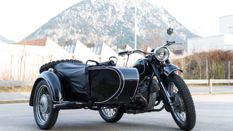A travel motorcycle is parked in front of the mountain ready for the road. All it needs is a travel camper to tow along and camp comfortably.