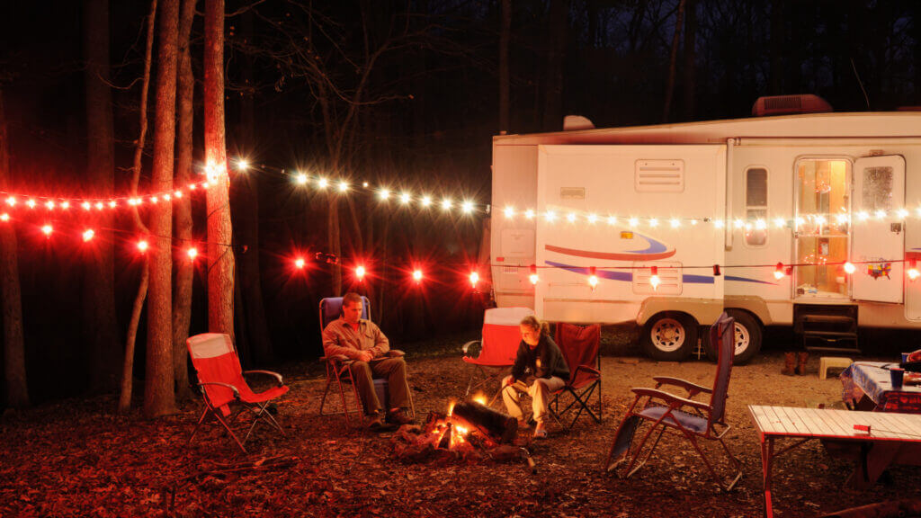 A couple sits alongside a fire with all of their RV lights on and string lights above their campsite. Are their RV electronics protected?