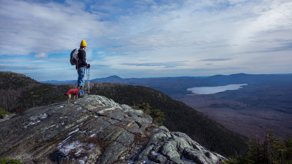 A man and his dog soak in the gorgeous view from a trail on the popular Maine Tumbledown mountain.