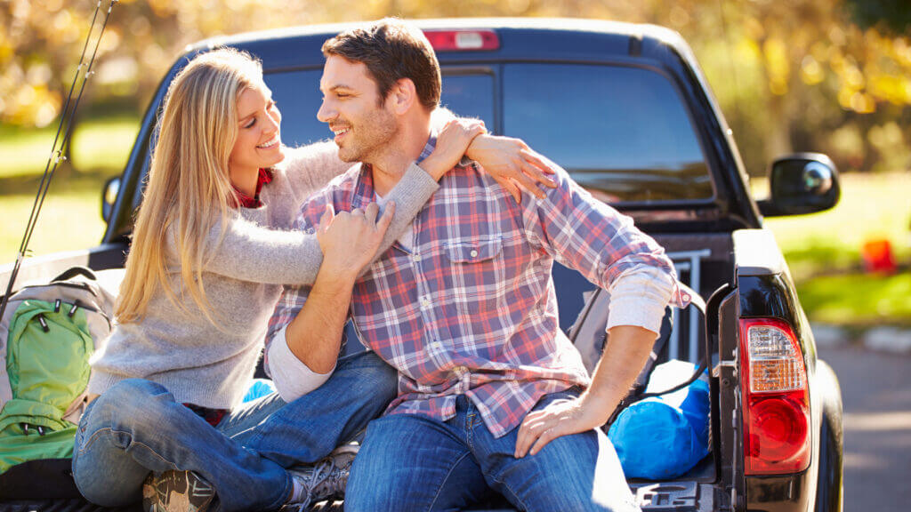 A couple smile lovingly and sit in the back of a truck bed ready to take off for an adventure.