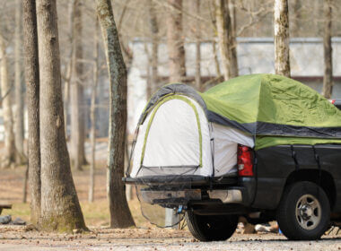 A truck is parked in a camping site with a truck bed tent in the back for convenient and comfortable camping.