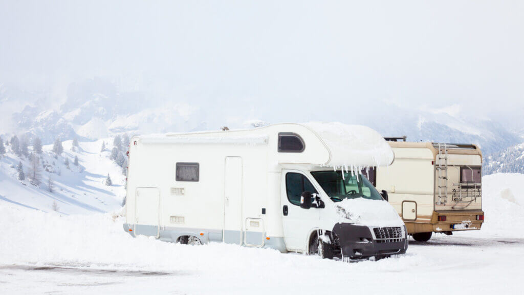Two RVs look frozen in the snow but can stay warm by following these tips.