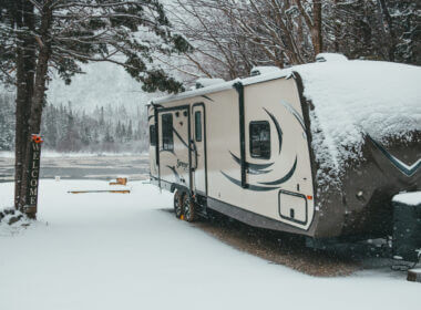 An RV is covered in snow and needs help to stay warm.