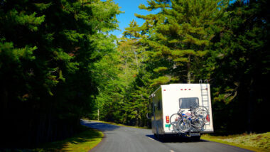 An RV with a bumper bike rack drives along a highway in a green forest.
