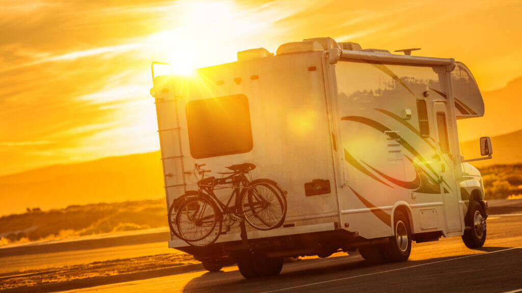 An RV with a bike locked into the bumper bike rack drives along a desert highway into the sunset.