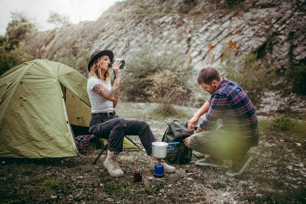A woman and man relaxing with a small tent while camping at Tarryall Reservoir. Mountains are lining the background.