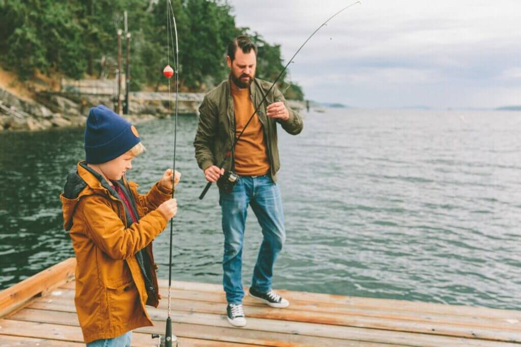 A father fishing with his son on a wooden pier with a green forest along the shorline. When camping at Tarryall Reservoir, fishing is a great activity.