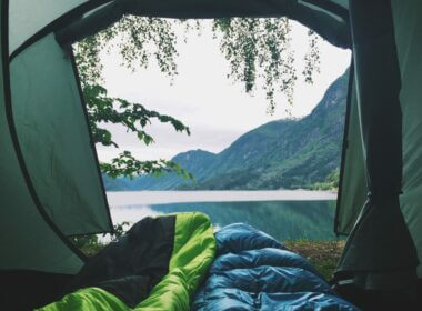 A couple camping at a lake looking out at the water from the tent.
