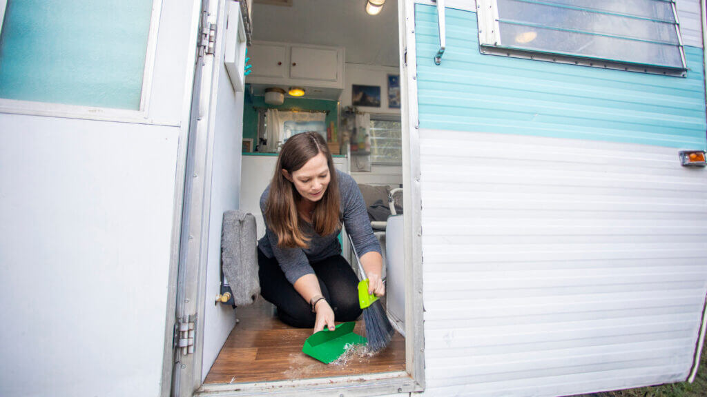 A woman uses a broom and dust pan to clean her RV but if she uses one of these 10 RV cleaning products her chores will be a lot more efficient.